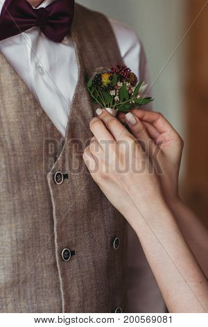 Delicate bride's hands adjust groom's boutonniere indoors
