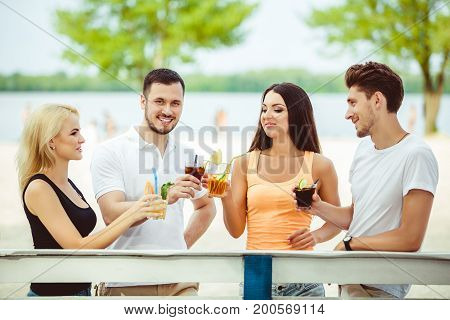 Friends having fun at the bar outdoors, drinking cocktails. Summer bar