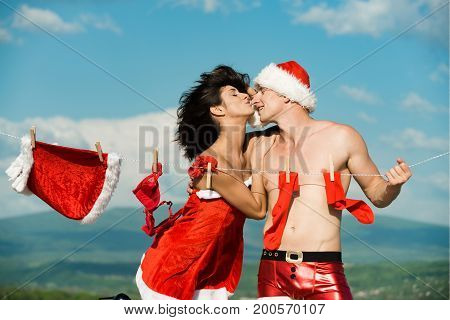 Xmas red costume on rope with pin. Laundry and dry cleaning. Couple of happy man and girl hanging clothes for drying. Christmas man and woman family. New year guy with muscular body on blue sky.