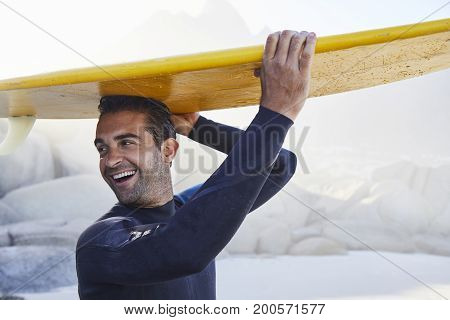 Laughing surfer guy in wetsuit with board on head