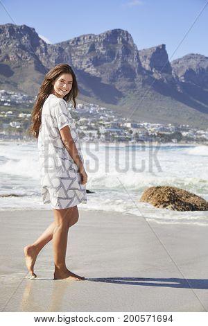 Brunette babe walking on beach in summer dress portrait