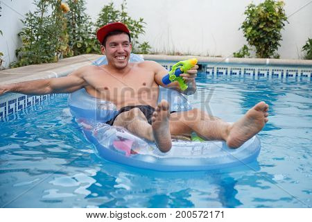 Young man sitting on inflatable and floating in pool shooting with water gun.
