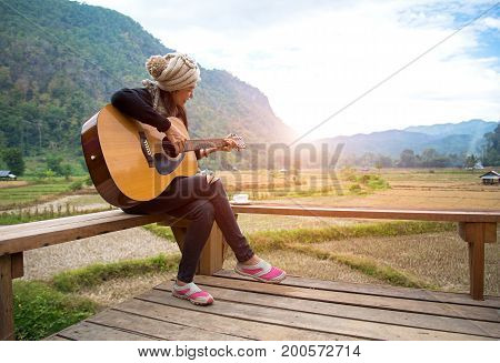 Traveler asian women playing acoustic guitar in the rice field