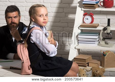 Schoolgirl And Dad With Serious Faces Hold Book And Glasses