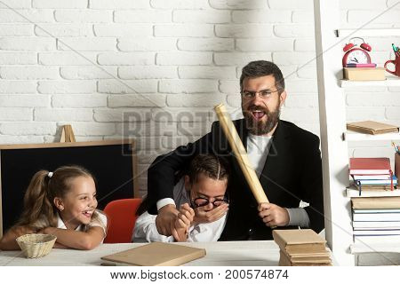 Father and schoolgirls on classroom background copy space. Kid elder sister and their dad with happy faces. Girls and bearded man sit at desk and have fun. Home schooling and back to school concept