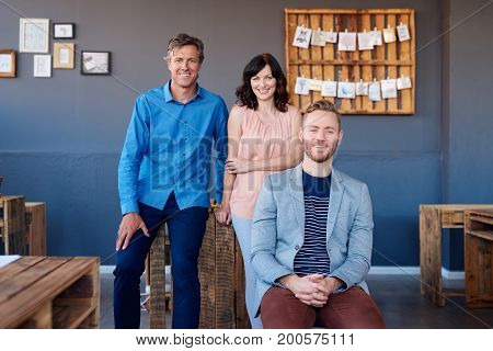 Portrait of a group of casually dressed work colleagues smiling confidently while working together in a large modern office