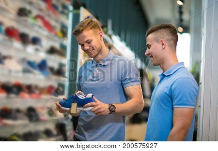 Two man deciding on new sports shoes in sports store