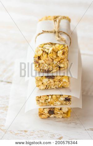 Stacked homemade muesli cereal bar with oats nuts raisins honey and dried apples. Lined with parchment paper tied with twine. White plank wood background. Healthy vegetarian snack.