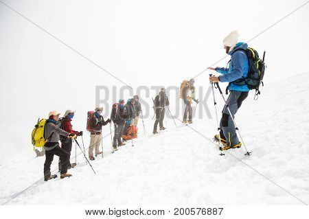 A team of climbers led by a guide discusses the upcoming climb against the background of a snow cat and mountains behind clouds