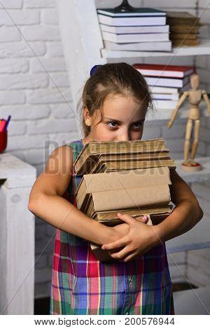 Girl Near Big Bookshelf With Textbooks. Schoolgirl With Tricky Eyes