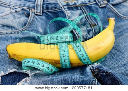 Health and male sexuality concept. Jeans zipper and pocket close up. Mens denim pants crotch with banana imitating male genitals. Banana wrapped with blue measure tape on jeans selective focus.