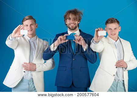 Business ethics concept. Happy men wearing formal suits. Businessmen showing blank cards. Information and cooperation. Group of people posing on blue background.