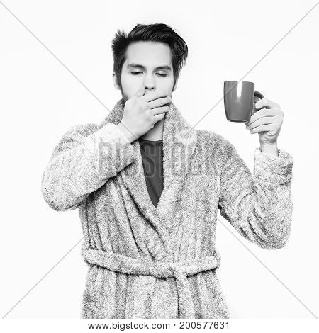 handsome yawning sleepy man or bearded sexy guy in blue terry bathrobe or dressing gown holds coffee or tea cup isolated on white background