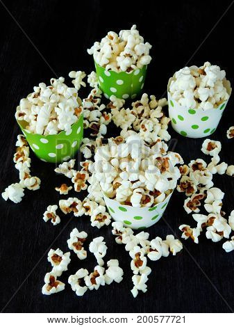 Popcorn in colourful assorted paper cups on a dark background