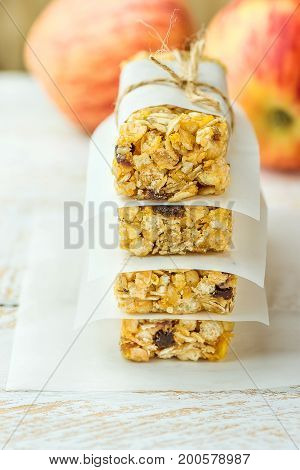 Stack of homemade muesli cereal bar with oats nuts raisins honey and dried apples. Lined with parchment paper tied with twine. White plank wood background. Healthy dessert..