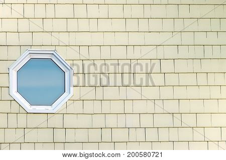 Octagonal whte wood frame window on building exterior with yellow painted siding. Background window on left with space for text in center and on right of image