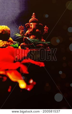 Happy Ganesh Chaturthi Greeting Card showing photograph of lord ganesha idol, pooja or puja thali, bundi laddu/modak, durva and hibiscus or jasvand flower