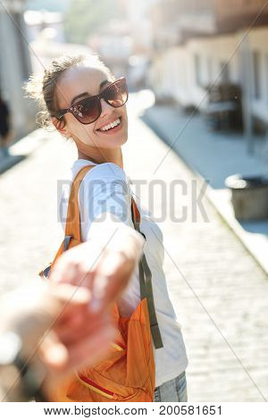 Young laughing girl outstretching hand asking to follow her on background of street