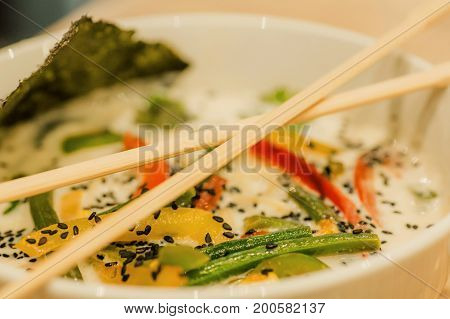 Asian soup with coconut milk and vegetables with spices. Tom yam style dish typical in Thailand. Thai food with chopsticks.