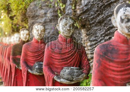 Buddhist monks stone statues row at Kaw Ka Thaung cave, Hpa-an, Myanmar