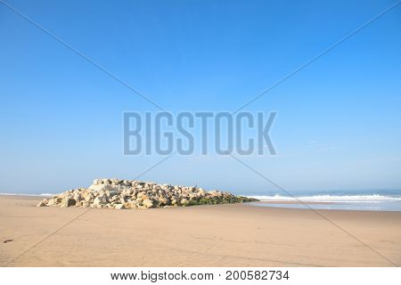 Beach at Atlantic ocean in France with stone surf breaker