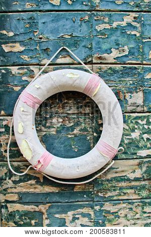A life preserver hanging on a weathered wall.