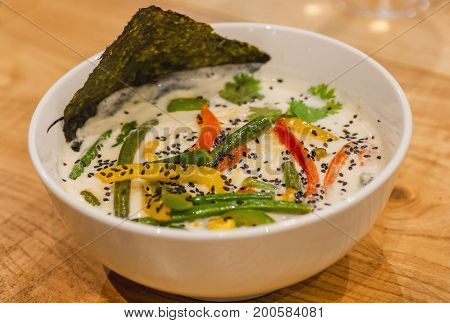 Hot thai soup with noodles coconut milk and vegetables served in white plate. Asian Tom yam style dish typical in restaurans of Thailand.
