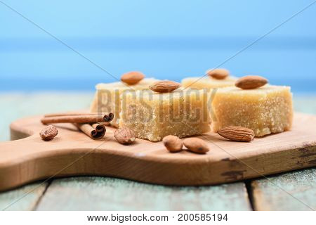Traditional Indian sweetmeats semolina halava with almonds on wooden board copyspace side view
