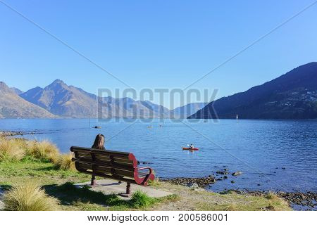 Young female sitting on the chair in Queenstown Garden located next to the town of Queenstown and Lake Wakatipu in Autumn South Island of New Zealand