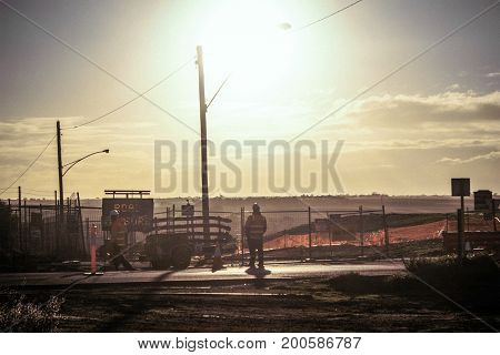 Two workers repairing the road in the afternoon.