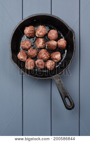 Beef meatballs prepared in cast iron pan on gray background copyspace above view with copyspace