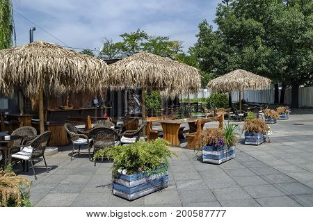View of cosy nook for summer relaxation below palm sunshade with bar, table, chair and wooden bench, park  Borisova