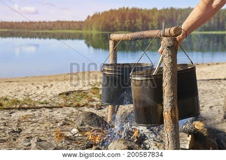 Hikers preparing breakfast on fire on the riverside in sunny morning