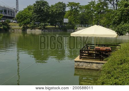 View of cosy nook for summer relaxation near at  lake Ariana  below  umbrella, with table, chair and wooden bench, park  Borisova gradina, Sofia, Bulgaria