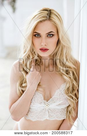 Fashionable female portrait of cute lady in white bra indoors. Close up beautiful sexy model girl in elegant pose. Closeup beauty blonde woman with hairstyle and makeup. Glamorous face with make up