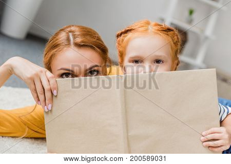 Mother And Daughter Hiding By Book
