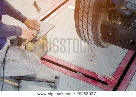 Electric wheel grinding on steel structure in auto repair shop