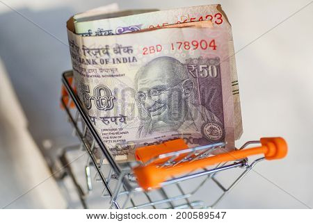 Shopping cart or trolley in India with namy rupees. Official currency of the Republic of India with smiley Gandhi portrait.