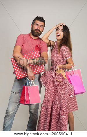 Shopping and fashion concept. Couple holding shopping bags and dress on grey background. Guy with beard and pretty lady doing shopping together. Bearded man with thoughtful face dressed in pink