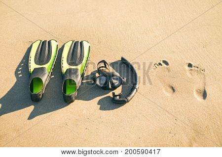 Swim flippers with snorkel, mask and feet steps on a sandy beach. Water sports. Snorkeling. Travel and holiday concept. Fins and scuba mask.
