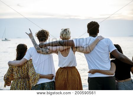 Group of diverse friends arm around at the beach together