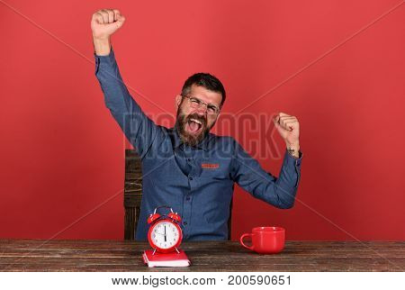 Exam and studying concept. Man with beard and glasses holds hands up red background. Cup retro clock and red book on vintage table. Professor with happy face sits at wooden table