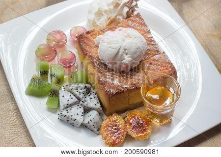 Honey toast on white dish with banana kivi grape and icecream.
