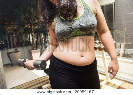 Fat woman weight loss lifting dumbbell in fitness gym