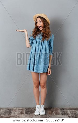 Image of happy young pretty woman standing over grey wall wearing hat holding copyspace in hand. Looking camera.