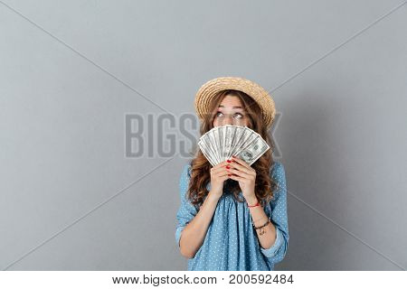 Picture of excited young happy woman standing over grey wall wearing hat covering face with money. Looking aside.