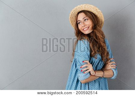 Picture of cheerful young pretty woman standing over grey wall wearing hat. Looking aside.