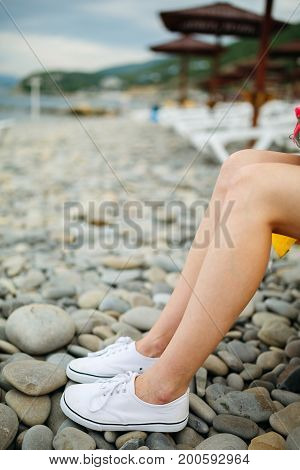 Crop shot of woman with naked legs wearing white sneakers and posing on pebble beach.