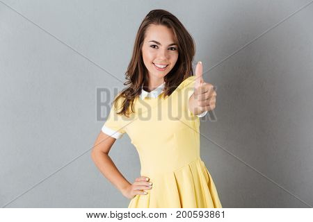 Pretty smiling girl in dress showing thumbs up gesture isolated over gray background