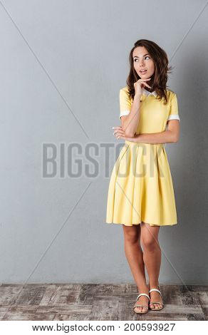 Full length portrait of a thoughtful young girl standing and looking away at copy space isolated over gray background